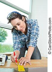 female carpenter taking measurements of a board