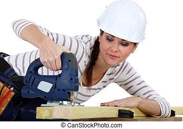 Female carpenter using a jigsaw.