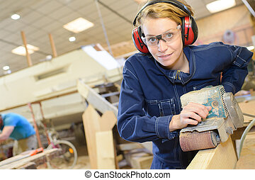 female carpenter using electric sander for wood