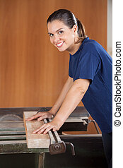 Female Carpenter Using Tablesaw In Workshop