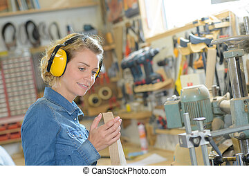 female carpenter with headphones in her workshop