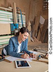 Female Carpenter Working On Blueprint In Workshop