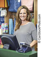Female Cashier At Sales Desk