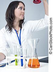 Female Caucasian Laboratory Staff Researching Liquids in Lab Glassware