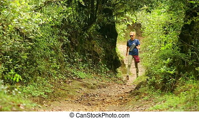 Female Caucasian tourist trekking walking along narrow footpath at himalayan mountains, Nepal