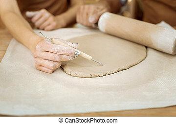 Female ceramist drawing some lines on future ceramic vase -...