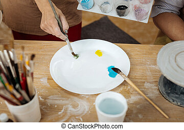 Female ceramist putting yellow and blue colors on white...