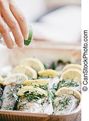 Female chef adding salt to fish dish. - Unrecognizable ...