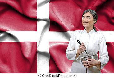 Female chef against national flag of Denmark