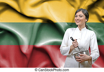 Female chef against national flag of Lithuania