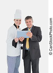 Female chef and businessman with digital tablet