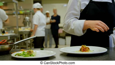 Female chef arranging food on plate in kitchen 4k