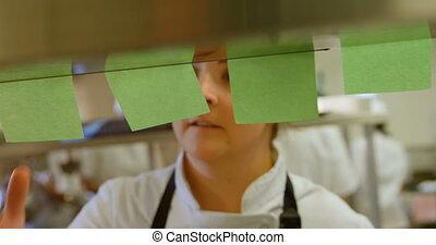 Female chef checking order in kitchen 4k