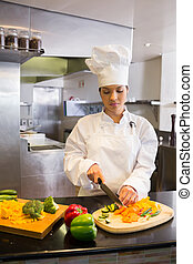 Female chef cutting vegetables in kitchen
