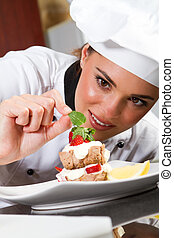 female chef decorating dessert - beautiful young female chef...
