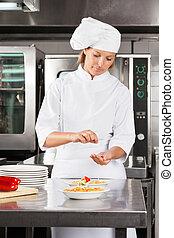 Female Chef Garnishing Dish At Counter