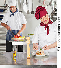 Female Chef Garnishing Dish In Kitchen