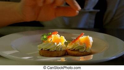 Female chef garnishing food on plate in kitchen 4k