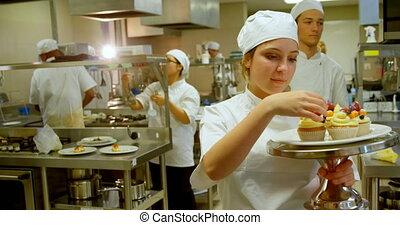 Female chef garnishing muffins in kitchen 4k