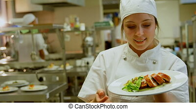Smiling female chef holding dish and showing ok sign 4k