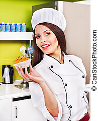 Female chef holding food. - Female chef holding food at...