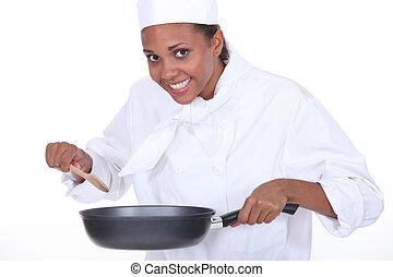 Female chef holding saucepan