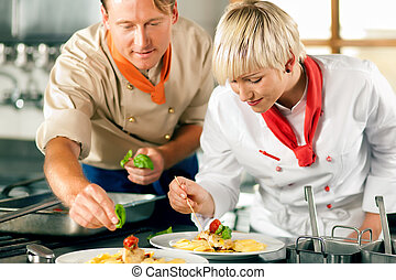 Female chef in a restaurant kitchen cooking - Two chefs in...