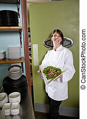 Female chef in restaurant with salad plate - Chef working in...