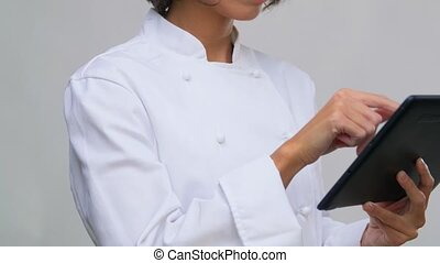 cooking, culinary and people concept - female chef in toque with tablet pc computer over grey background