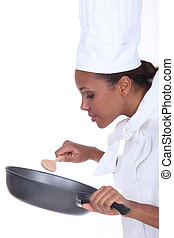 Female chef in uniform stirring a non stick pan
