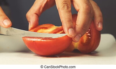 Female chef is chopping fresh juicy tomato on the cutting board in restaurant's kitchen