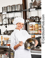 Female Chef Mixing Egg With Wire Whisk In Bowl