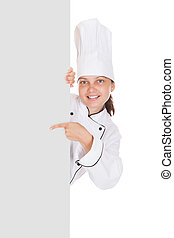 Female chef pointing on blank placard