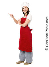 Female chef pointing towards copy space area