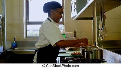 Female chef preparing food in kitchen at restaurant 4k