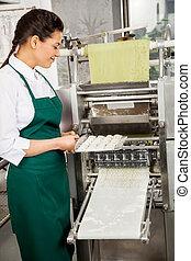Female Chef Preparing Ravioli Pasta In Machine