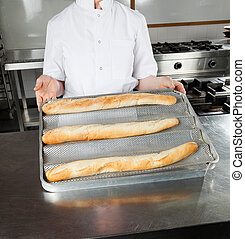 Female Chef Presenting Loafs In Kitchen
