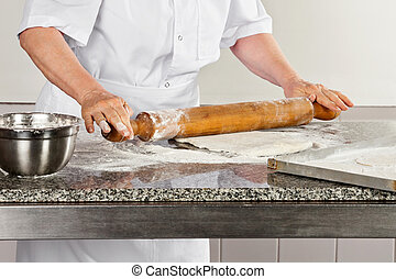 Female Chef Rolling Dough - Midsection of female chef...