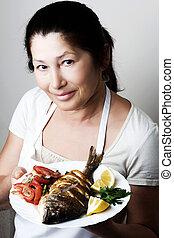 Female chef shows sea bream fish with lemon, parsley, garlic