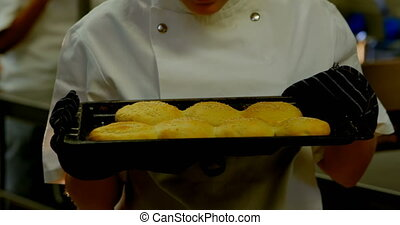 Female chef smelling tray of cookies in kitchen 4k