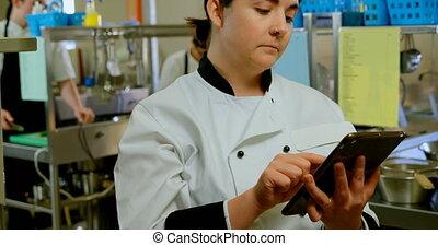 Female chef using digital tablet in kitchen 4k