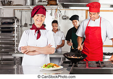 Female Chef With Arms Crossed In Kitchen