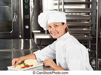 Female Chef With Dish At Counter