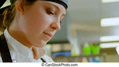 Female chef working in kitchen at restaurant 4k