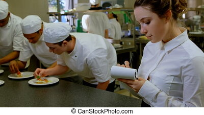 Female chef writing on notepad in kitchen 4k