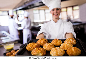 Female chefs holding baking tray of kaiser rolls in kitchen