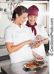 Female Chefs Using Digital Tablet In Kitchen