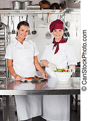 Female Chefs With Dishes At Kitchen Counter