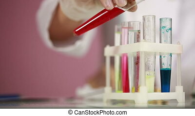 Female chemist comparing test tubes with chemicals. protective glasses