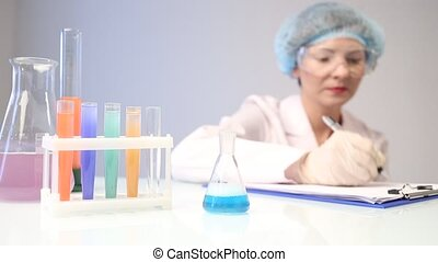 female chemist pouring a blue liquid into a chemical flask. writes the results